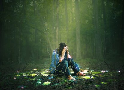 Woman in a green forest face covered by hands sitting on the ground in sadness