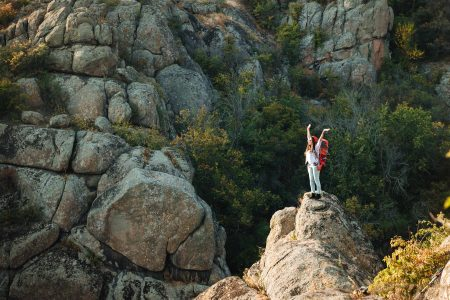 woman standing on a cliff with hands lifted high in full surrender to God