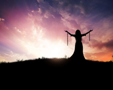 woman standing holding up arms to God with broken chains hanging from them as she is free and no longer a prisoner to sin