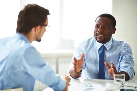 Image of two young businessmen interacting at meeting in office one is sharing his faith