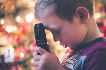 Child holding a Holy Bible leaning head down to touch bible side view