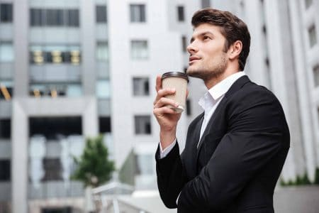 Businessman standing in thought holding a coffee cup. Are you devoted to God or only lukewarm?