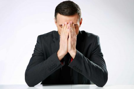 Man looking worried with head bowed and hands folded in prayer