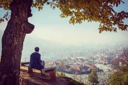Man sitting alone on park bench overlooking the city.