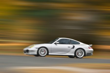 A modern sports car speeding along the road with a motion blur effect. Alluding to the good life